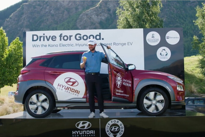 Photo of Sam Eade with a Hyundai Kona after winning the Drive For Good hole in one