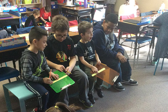 Two fifth graders and two kindergarteners work together holding clipboards and rulers