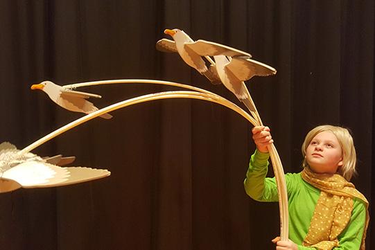 Boy holding bird flying prop