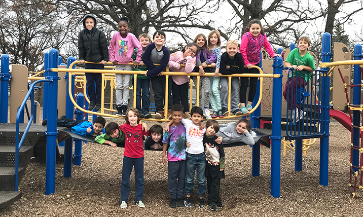 Tate Woods class standing together on the playground bridge