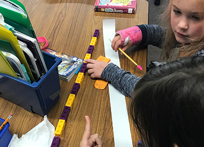 Elementary students work through multiplication activities