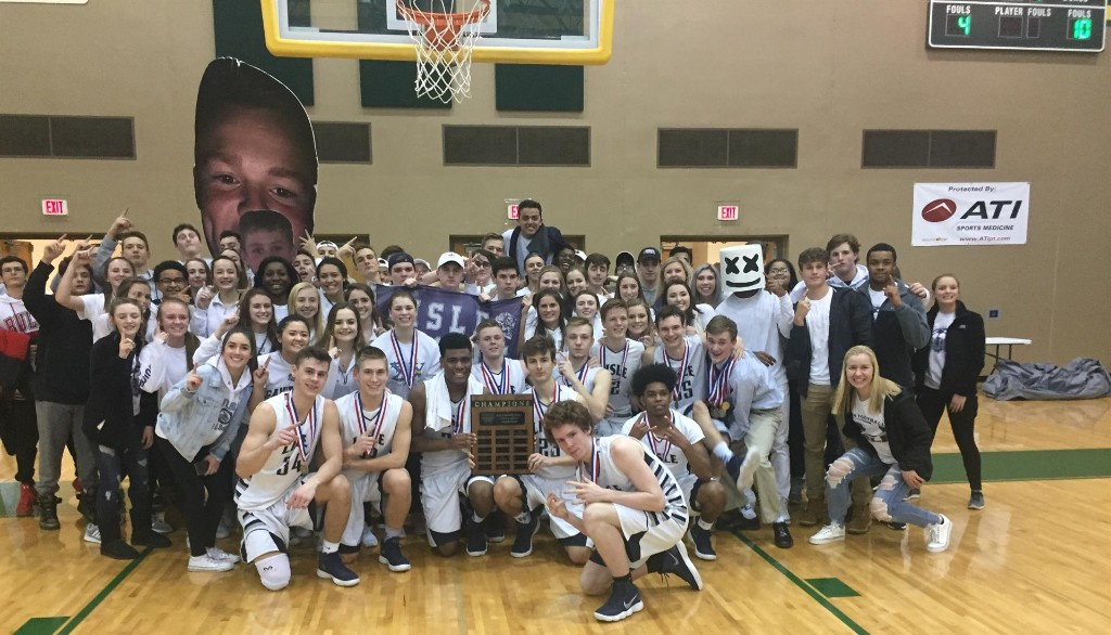 Boys Basketball team and fans hold conference title plaque