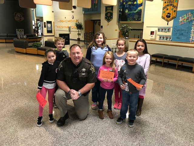 Tippecanoe County Sheriff Deputy Rob Rush, who serves as a School Resource Officer for Tippecanoe School Corproation, poses in Cole's lobby with seven students. Officer Rush is kneeling with the seven students around him. All wear a smile.